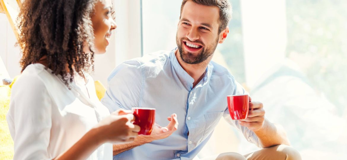 Sharing great ideas. Happy young African woman and young man holding cups of coffee and discussing something while sitting together near the window